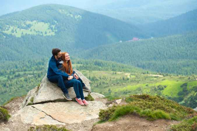 photo of couple sitting on rock