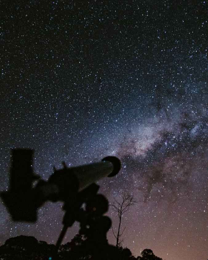 telescope pointing at milky way galaxy at night