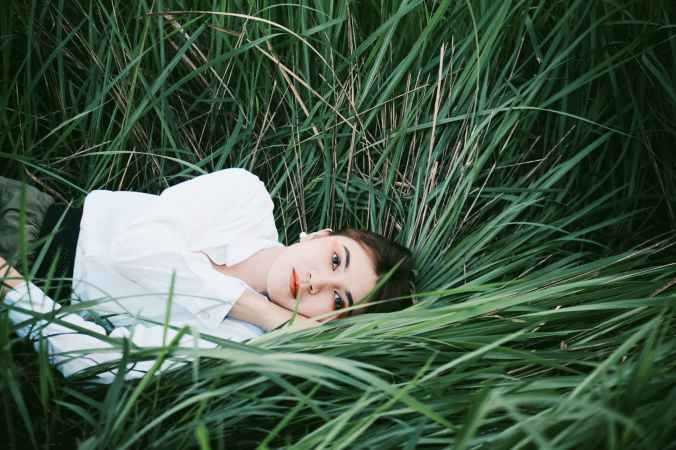 woman lying down on blades of grass