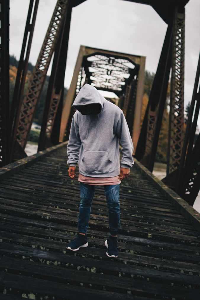 man in gray pull over hoodie standing on train rail